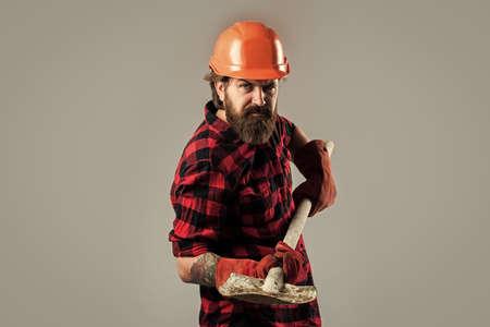 He needs a little break. confident construction engineer. professional architect hold shovel in gloves. repair and building. serious worker wear hard hat. brutal builder in helmet. bearded repairman 版權商用圖片