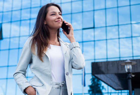 girl speak on phone outdoor. beautiful lady in stylish clothes. female beauty and fashion. ceo businesswoman with smartphone. business communication. confident woman in formal elegant suit. Be happy 免版税图像