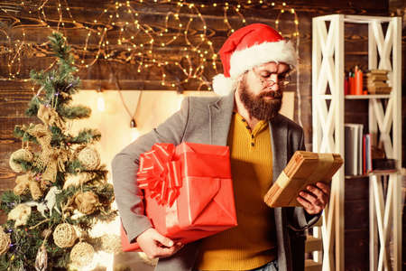Bearded guy wear santa claus hat carry christmas present box. Delivery christmas present. Christmas gift. Man santa hat hold gift. Delivery service. Spread happiness and joy