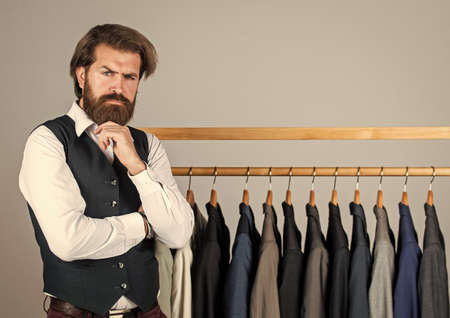 Man clothing in boutique. Man with suit. tailor in his workshop. Handsome bearded fashion man in classical costume suit. Man in custom tailored suit presenting expensive tuxedo. Another client