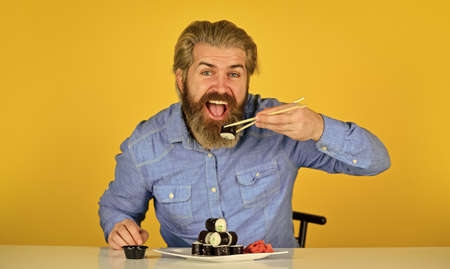 Japanese cuisine. Traditional food in Japan. Chief meal Fast service. asian meal. sushi roll dish take away. Sushi delivery. happy man eat sushi. sushi and ginger with chopsticks