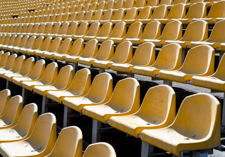 concept of fans. chairs for audience. cultural environment concept. color and symmetry. empty seats. modern stadium. yellow tribunes. seats of tribune on sport stadium. empty outdoor arena