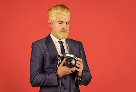 Fashion portrait of man. confident businessman hold retro camera. mature man dyed beard and hair. professional photographer make photo. male beauty. capture result of barbershop salon. vintage camera 免版税图像