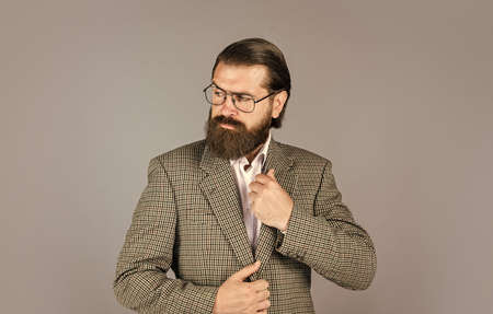 serious bearded man. handsome and successful man in expensive suit. He is in white shirt and glasses. stylish successful man in suit posing. business man wear suit. official office lifestyle Foto de archivo
