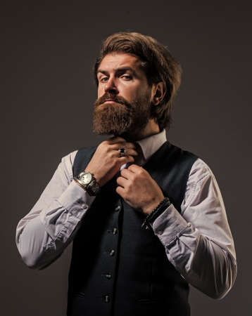 fixing bow tie. stylish successful man in suit posing. business man wear suit. official office lifestyle. serious bearded man. handsome successful man in expensive suit. He in shirt with hand watch