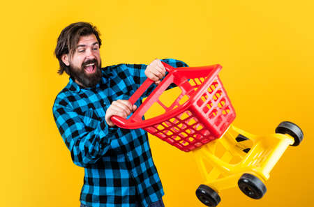 crazy driver. handsome hipster wear checkered shirt in shop. mature shopper go shopping in mall. bearded man carry shopping cart. brutal guy making purchase. male fashion style