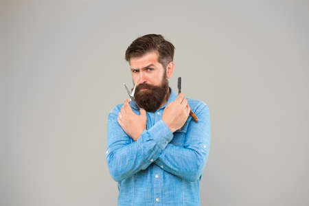 Shaving with a real blade sounds cool. Bearded man prepare shaving tools yellow background. Hipster hold shaving razor and scissors. Professional shaving from master barber. Shave barbershop Archivio Fotografico