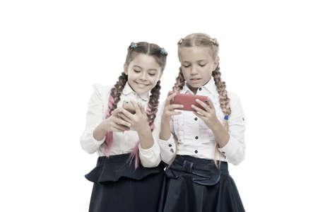 Worldwide net. Internet resource has hazards for kids. Girls school uniform surfing internet. Schoolgirls use mobile internet smartphone. School application smartphone. Mobile addiction. Modern life