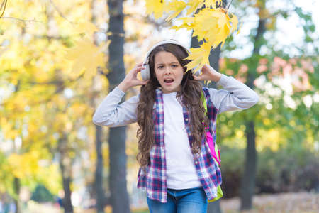 Irritated little girl suffer from loud unpleasant music sound cacophony in autumn park outdoors, headphones