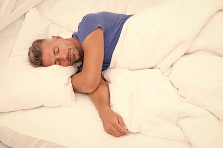 Sexy man lying on bed with soft pillows at home. Perfect morning. Tips sleeping better. male health. Enjoying time at home. Relaxing in bedroom. day dreaming male. Day sleeping. Morning of a new day