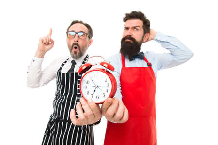 Lack of time. Check what time is it. It is lunch time. Men cooks with alarm clock. Failed deadline. Man bearded hipster and mature chef apron white background. Working hours and lunch break