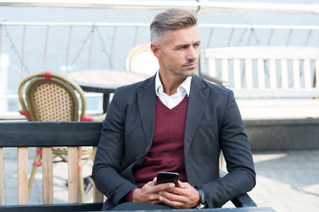 Better way to live. Professional man rest in outdoor cafe. Handsome man in formal style. Fashion look of businessman. Office style. Business communication. Mobile technology. 3G. 4G