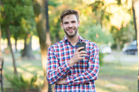 smiling unshaven man drinking morning coffee in checkered shirt outdoor, inspiration