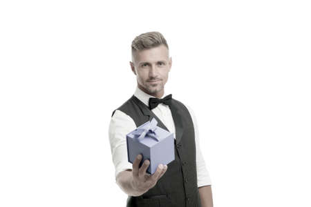 Gentleman delivering gift. Handsome man with wrapped gift box. Happy businessman hold present in hand. Birthday holiday. Shopping mall. Shop purchase. Gift package. Womens day. Valentines day Stock Photo