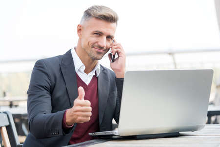 Happy businessman show thumbs up hand gesture talking to client on mobile phone and using computer for business online, approval 免版税图像