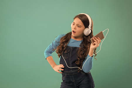 small girl use mp3 player. study in modern life. schoolgirl use digital device. casual fashion for kids. kid long hair listen music in headset. small child make play list on smartphone. copy space