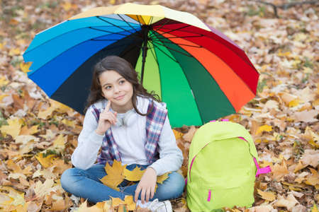happy kid in casual style spend time relaxing in autumn park enjoying good weather under colorful umbrella, optimistic mood Stock fotó