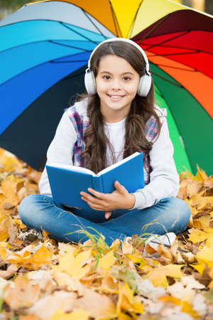 autumn kid under colorful umbrella. feel the inspiration. happy childhood. back to school. girl read book wearing headset in park. enjoy fall in forest. listen to music. online courses education