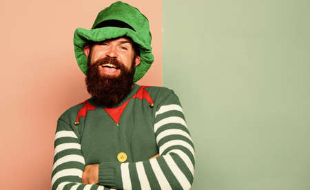 Bearded elf. Winter carnival. St Patricks day. Hipster with beard wearing green costume for party. Cheerful man celebrate holiday. Christmas elf. Elf concept. Traditions or customs. Happy celebration