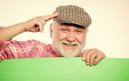 Pensioner grandfather in vintage hat hold poster information copy space. Event announcement. Announcement concept. Advertisement shop. Senior bearded man peek out of banner place announcement