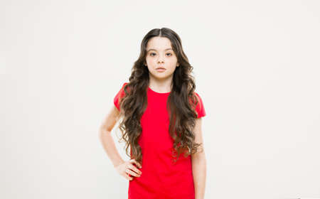 Kid cute face with adorable curly hairstyle. Little girl grow long hair. Teen fashion model. Styling curly hair. Change you can see. Hairdresser tip. Kid girl long healthy shiny hair. Perfect curls Stock fotó