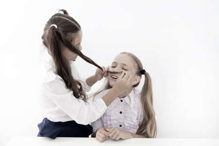 Girls make mustache with long hair. Lets imagine you were boy. Girl cheerful playful mood play with hair as mustache. Masculinity and femininity concept. Hairstyle fashion. Schoolgirls tidy uniforms 免版税图像