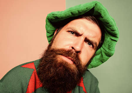 Who is there. Picky man looking at camera. Bearded elf. Winter carnival. St Patricks day. Hipster with beard wearing green costume for party. Christmas elf. Elf concept. Traditions or customs