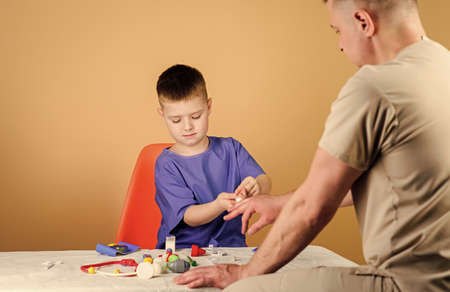 Kid little doctor sit table medical tools. Health care. Pediatrician concept. Medical examination. Boy cute child and his father doctor. Hospital worker. Medical service. Analysis laboratory