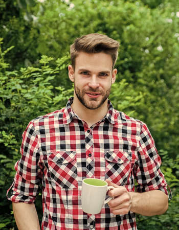 What a great morning. cheerful man in shirt drink morning coffee. good morning. fresh inspiration and energetic beverage. handsome bearded guy drinking tea outdoor. he loves cocoa. food and drink Фото со стока