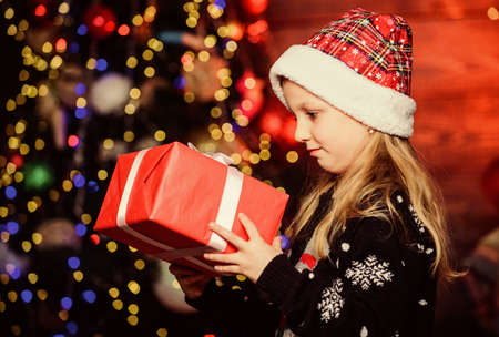 Winter shopping. Holiday party that actually sounds fun. Merry christmas. Kid adorable wear santa hat celebrate christmas. Buy christmas gift. Girl cute child hold wrapped gift near christmas tree