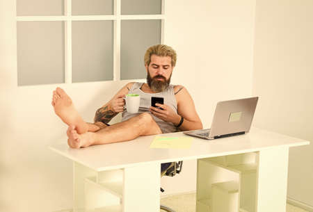self quarantine routine. Serene barefoot guy resting, remote workday with computer. networking while staying at home. Technology. Handsome man using laptop at home. Making great decisions