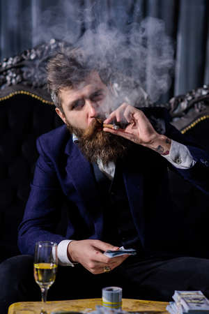 Bearded man with confident face and money in classic interior.