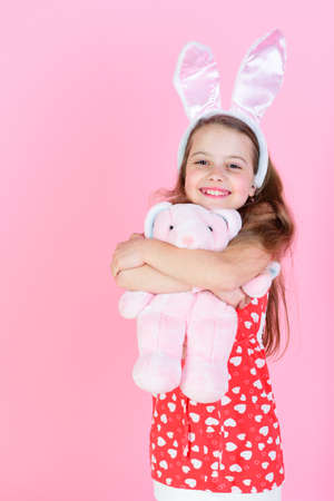 Childhood, youth and growth Happy girl hugging rabbit toy on pink background.