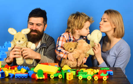 Parents and kid cuddle with toys. Man, woman and boy