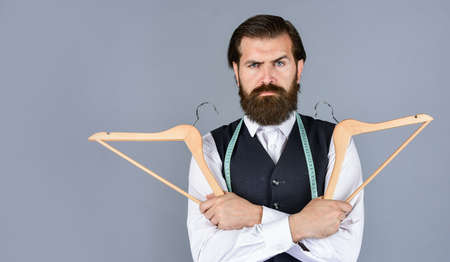 real professional. professional male sartor with measuring tape and hanger. Handsome man in smart casual wear is holding hanger. portrait of man holding hanger. tailor man use tape measure