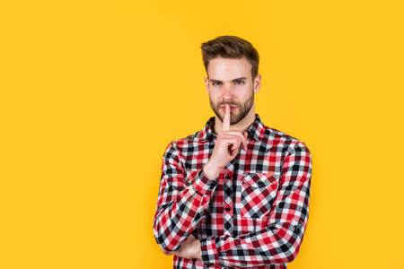 keep the secret. handsome casual man standing with beard and bristle. cheerful and stylish. handsome man on red background. portrait of european businessman. confident and calm. copy space