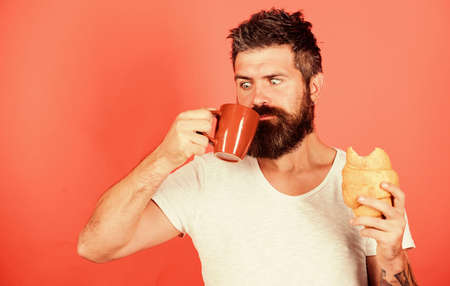 Bearded hipster enjoy breakfast drink coffee. Morning tradition concept. Unhealthy but yummy breakfast. Fresh baked croissant. Delicious breakfast. Man start morning with coffee and croissant