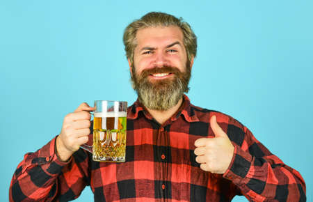 porter beer. leisure and celebration. Man drinking in pub bar. Beer with foam. brutal hipster drink beer. mature bearded barman hold beer glass. confident bartender raising toast