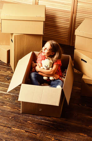 Tranquility Inside. happy little girl with toy. Cardboard boxes - moving to new house. purchase of new habitation. repair of room. new apartment. happy child cardboard box