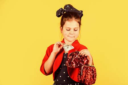 Born to be rich. Little girl put dollars in money bag. Small child save cash money. Money savings. Deposit money into savings account