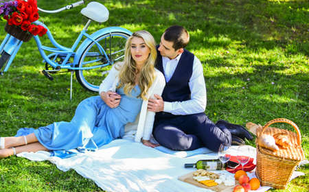 Man and woman in love. Couple in love enjoy picnic time. Spring date. Playful couple having picnic in park. Romantic date. Celebrate love. Couple cuddling relaxing at green meadow with picnic basket