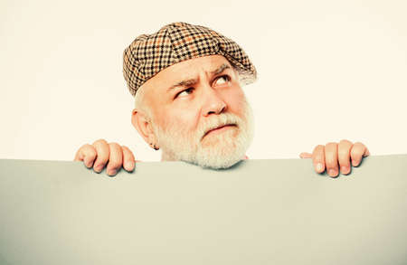 Charming pensioner in vintage hat hold poster information copy space. Public information. Announcement concept. Senior bearded man peek out of banner place information. Advertisement elderly people Banco de Imagens