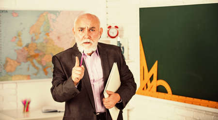 you should study. bearded man give marks. write notes in book. strict senior lecturer make notes. teacher of geography. classroom with map and blackboard. back to school. math education in school