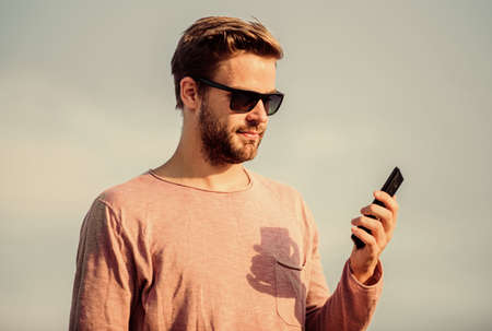 Important mobile conversation. Application and internet. Hipster wear sunglasses hold mobile phone sky background. Hipster smartphone call. Man mobile call. Stay in touch. Mobile call concept Banco de Imagens