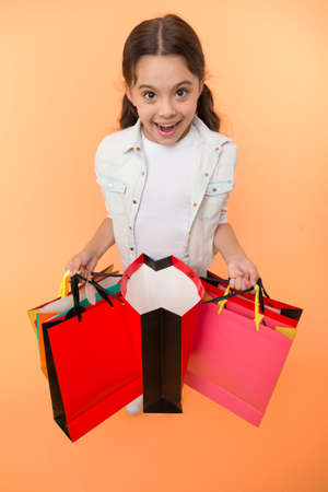 Check out her profitable purchases. Girl carries shopping bags yellow background. Girl fond of shopping. Child cute shopaholic with bunch shopping bags black friday total sale. Exciting shopping