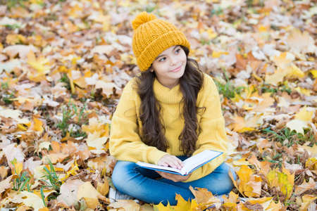 Small child read book with thoughtful look sitting on autumn leaves outdoors, imagination