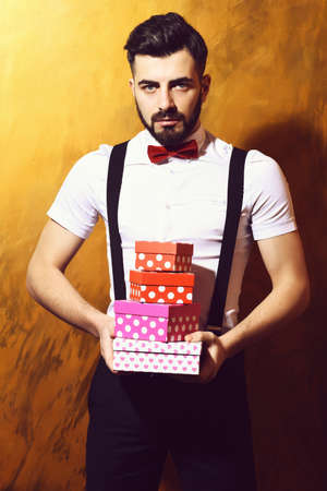 bearded man holding present boxes with serious face 免版税图像