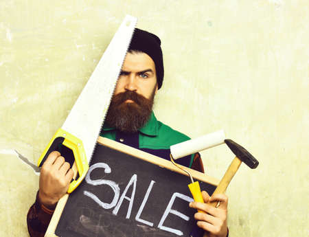 bearded man holding various building tools and board, serious face 写真素材