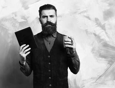 Bearded brutal caucasian hipster with coffee cup and black notebook 免版税图像 - 157884525