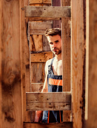 Scaffolding and frameworks. Planning construction. Man builder in work clothes. View through scaffoldings. Handsome builder at construction site. Guy works at construction. Woodworks concept